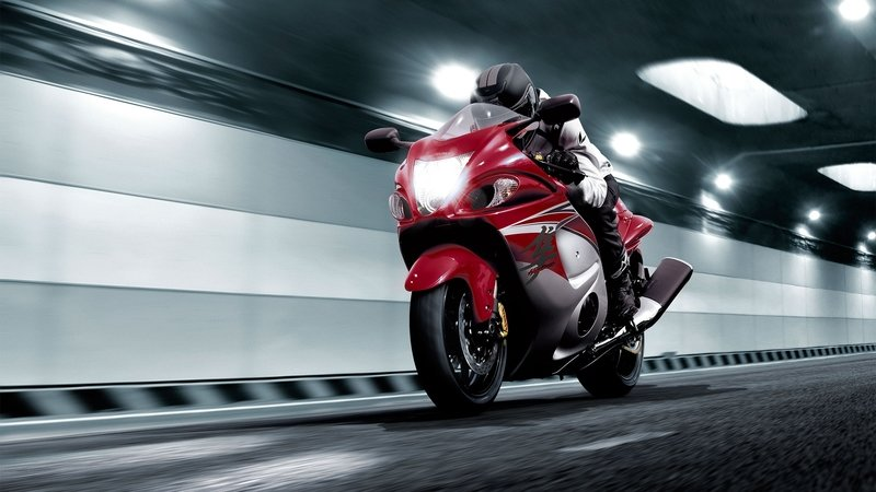 A red Hayabusa motorcycle speeding through a tunnel