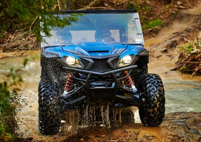 A blue Yamaha wolverine side-by-side crossing a muddy creek bed