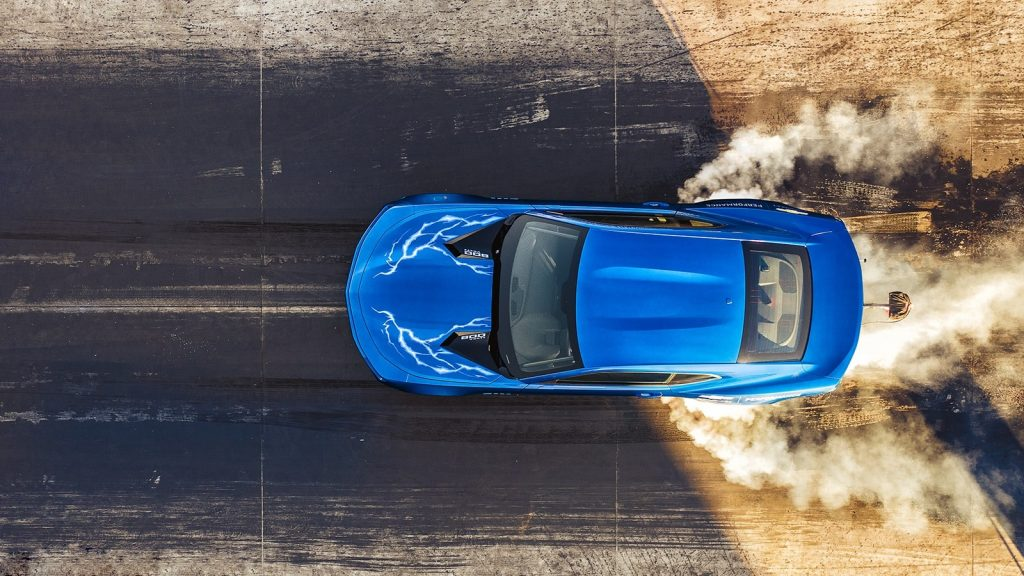 An overhead shot of a blue 2020 Chevrolet 50th Anniversary COPO Camaro does a burnout on the dragstrip