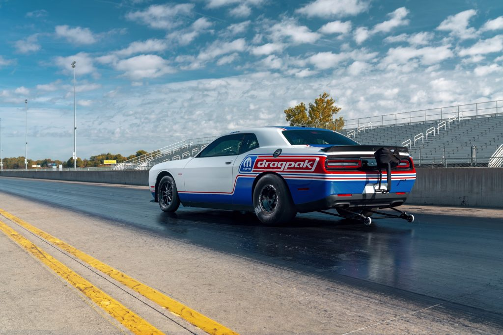 Rear view of the red-white-and-blue-liveried 2020 Dodge Challenger Drag Pak on a drag strip, showing the rear-mounted wheelie kit