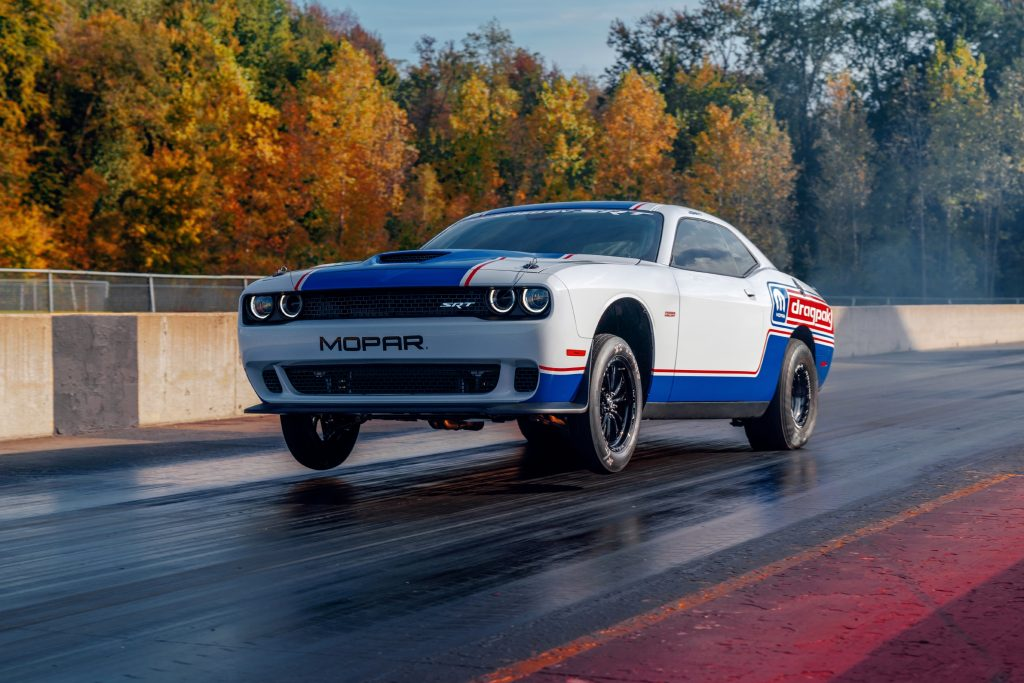 Red-white-and-blue-liveried 2020 Dodge Challenger Drag Pak pulling a wheelie on the drag strip