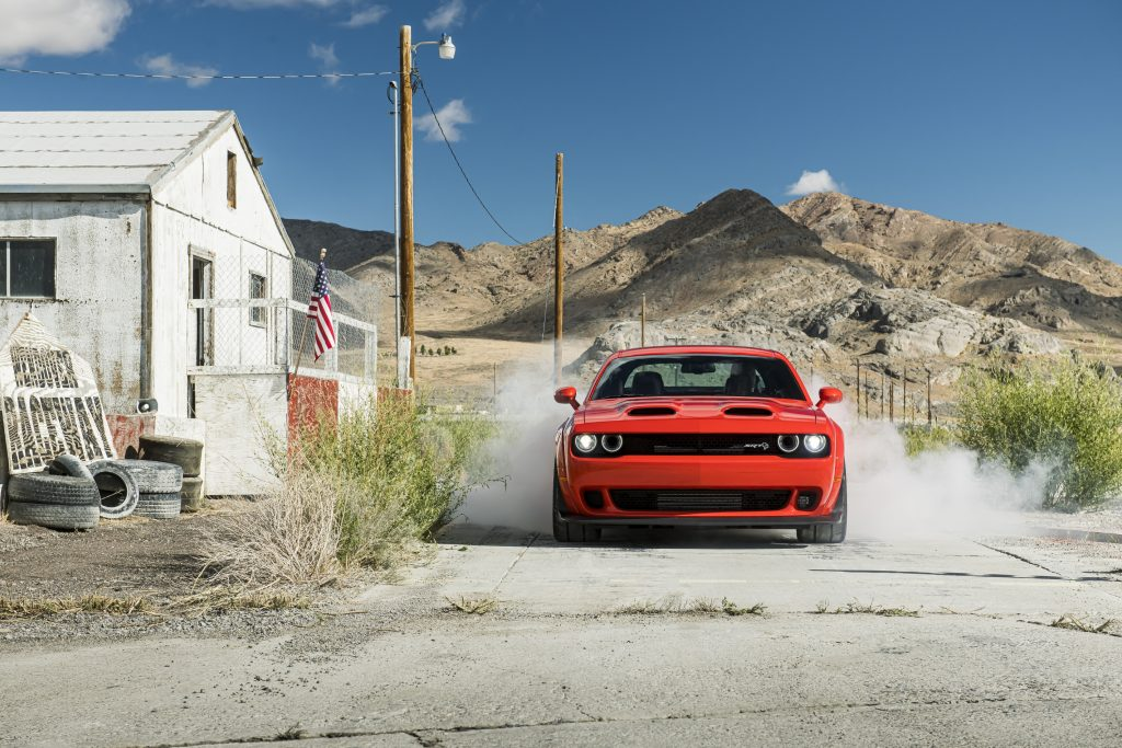 Red 2020 Dodge Challenger SRT Super Stock doing a burnout in an old desert town