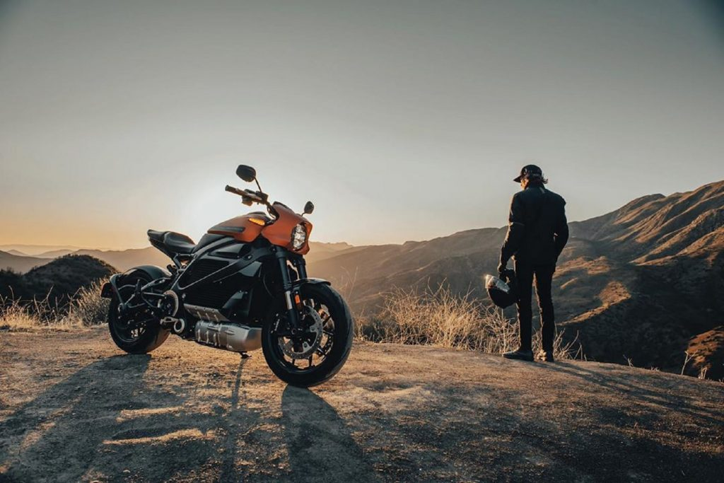 Orange 2020 Harley-Davidson LiveWire with its rider in the background, both watching the rising sun over a canyon