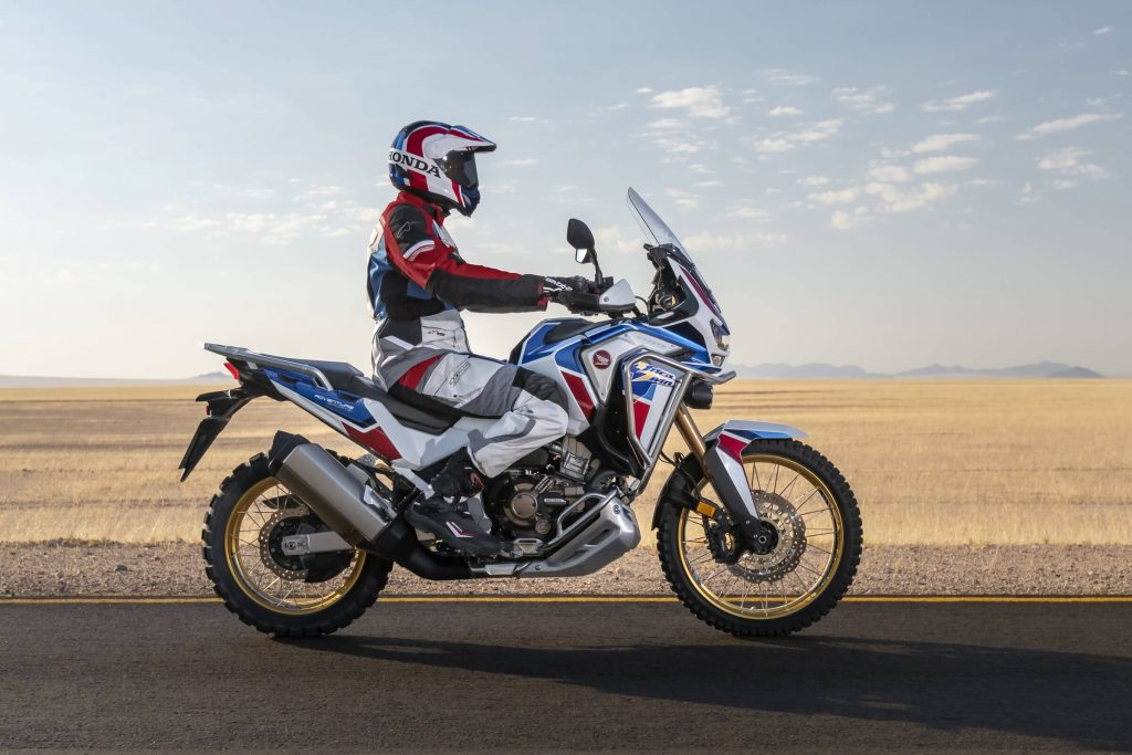 White-blue-and-red-liveried 2020 Honda Africa Twin Adventure Sports, side view, driving down a desert road
