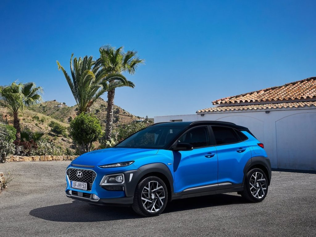 A blue Hyundai Kona Hybrid sits in a driveway lined with palm trees.