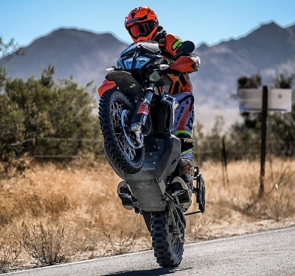 A rider wheelies a 2020 KTM 790 Adventure R, showing the Black Dog Ultimate skid plate