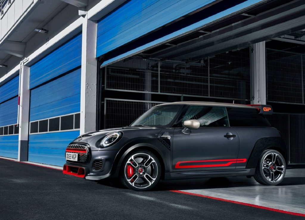 A black-and-red 2020 Mini Cooper JCW GP coming out of a blue track-side garage