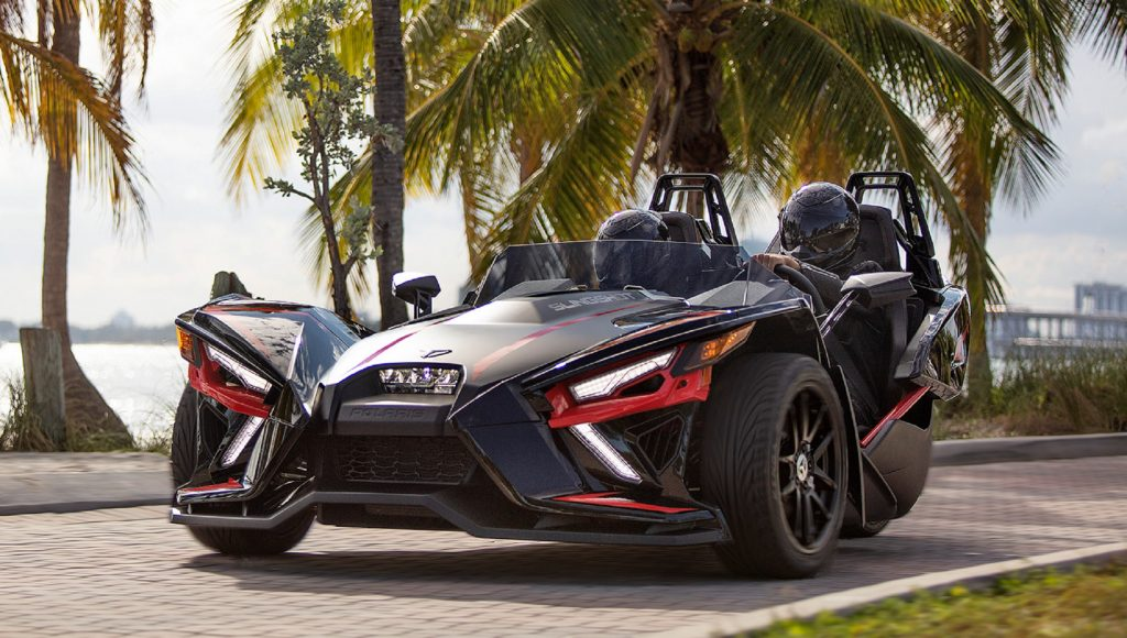 A black-and-red 2020 Polaris Slingshot R in front of a palm-tree-lined marina