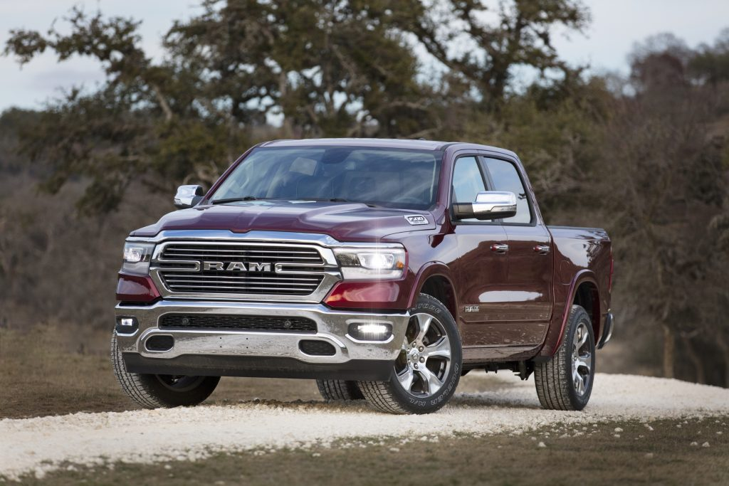 A burgundy Ram 1500 Laramie sits in the curve or a dirt road.