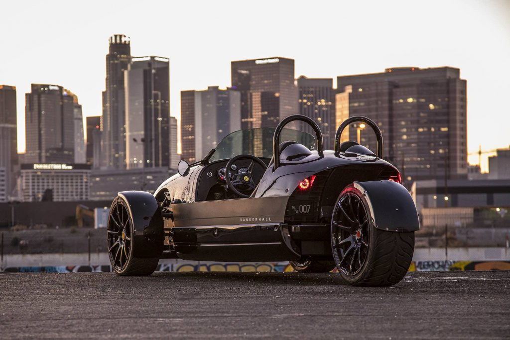 Rear view of the electric 3-wheeled 2020 Vanderhall Edison 2 in front of a cityscape