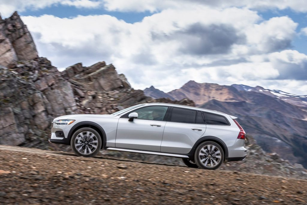 A white 2020 Volvo V60 sits at the foothillls of a mountain range.