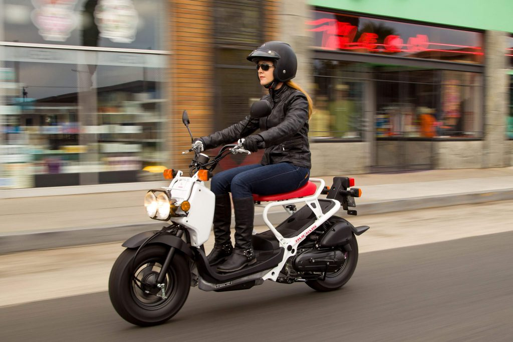 Riding a white 2020 Honda Ruckus in the city