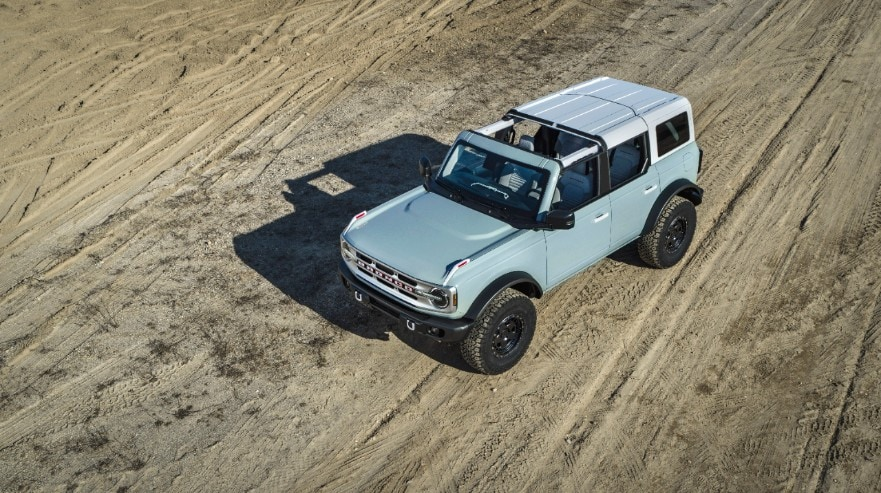 overhead light blue 2021 Ford Bronco with front roof removed bombing through the desert