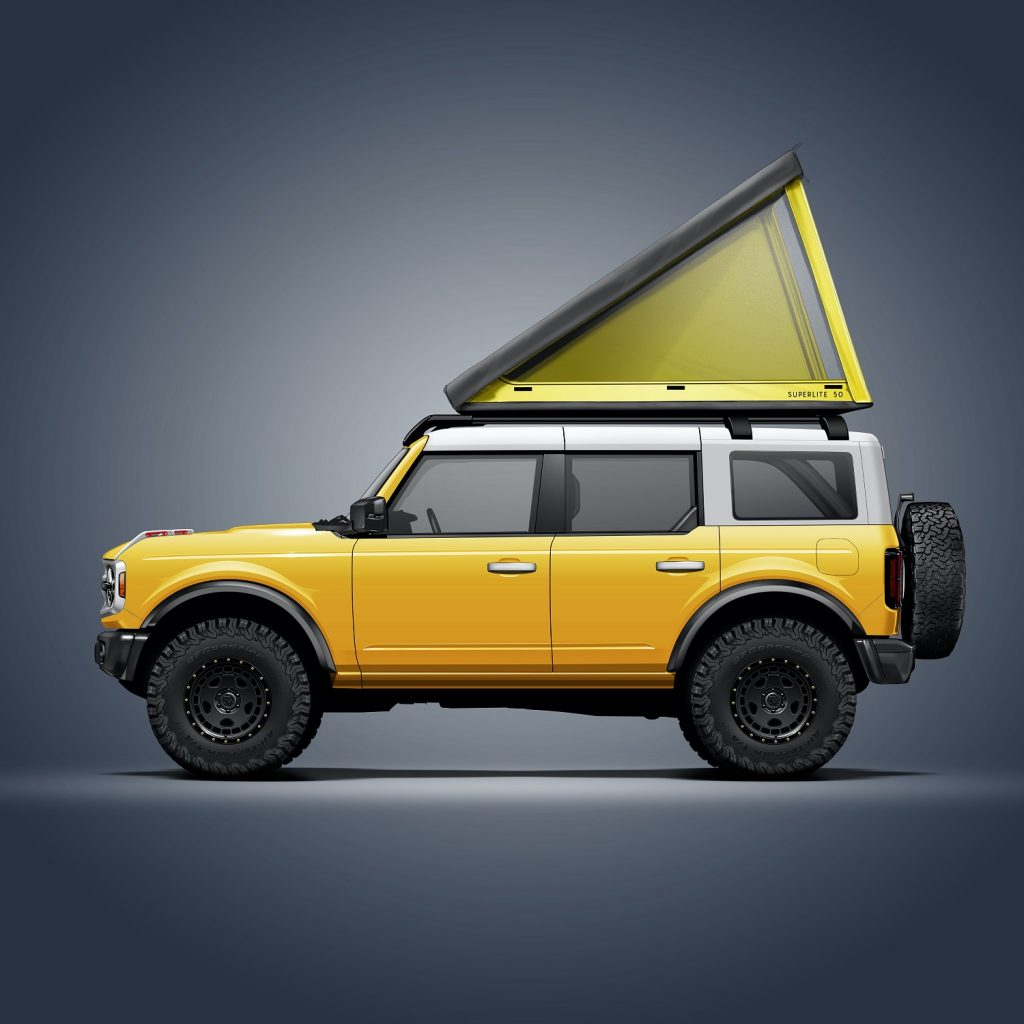 A yellow 4-door 2021 Ford Bronco with a Go Fast Campers SuperLite rooftop tent