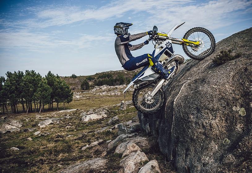 The 2021 Husqvarna 2-stroke TE 250i enduro bike riding up a large boulder