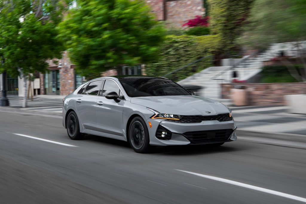 A gray 2021 Kia K5 sedan, successor to the Kia Optima, passes through a downtown city street.