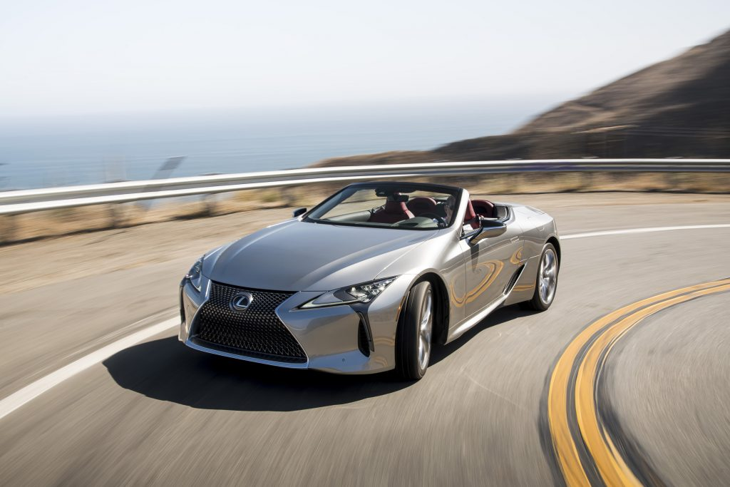 A silver, topless 2021 Lexus LC 500 Convertible rounds a turn on a coaster road.