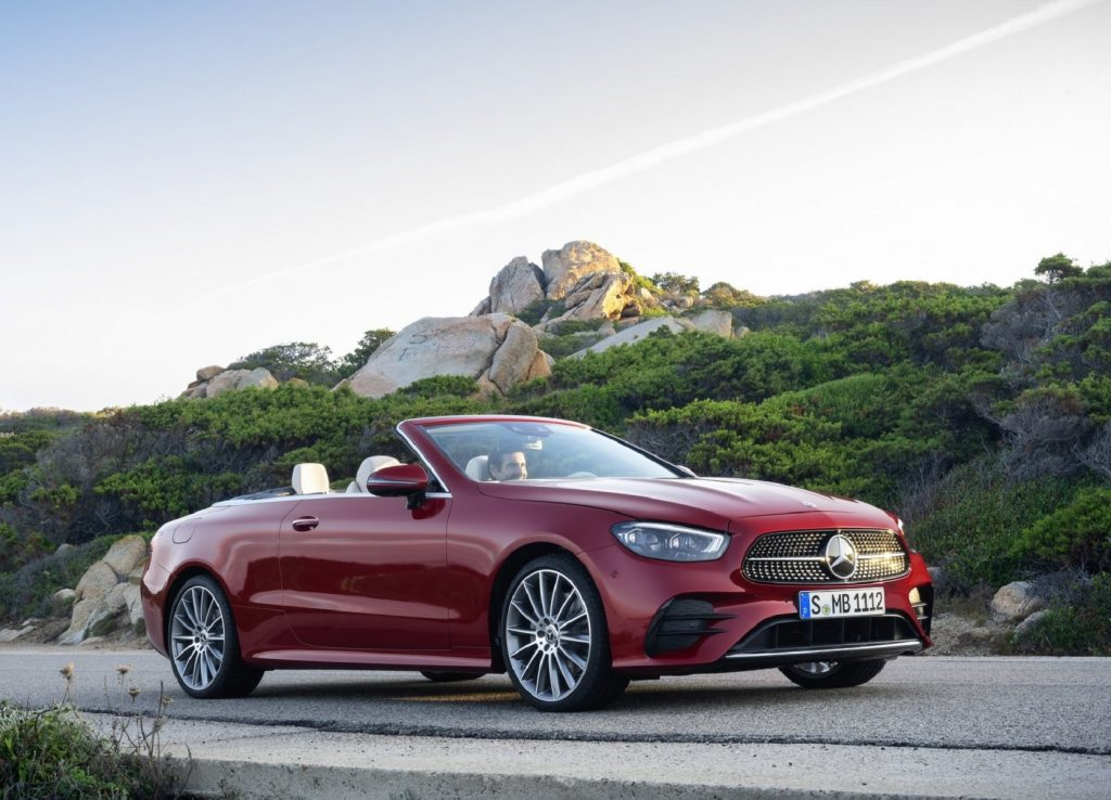 A red 2021 Mercedes E-Class Cabriolet in front of a green-covered rocky hill with its top down