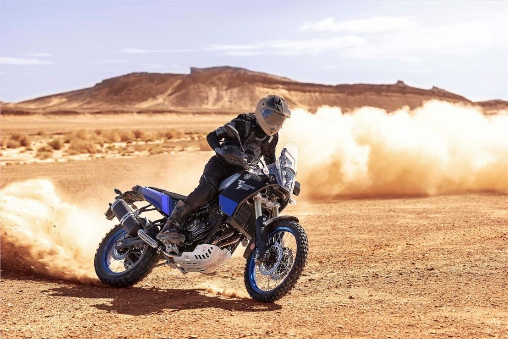 A blue-tanked 2021 Yamaha Ténéré 700 adventure bike power-sliding in the desert