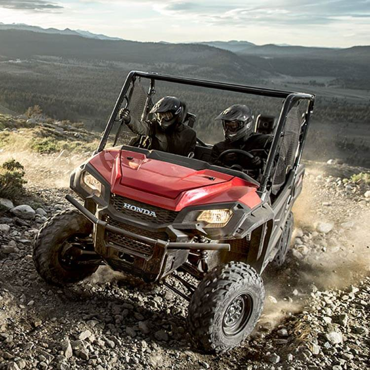 a red Honda Pioneer side-by-side UTV scrambling up a rocky incline.