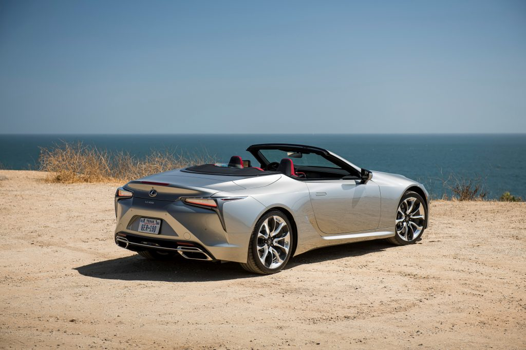 A silver 2021 LC 500 Convertible sits at a beach with the top down | Lexus