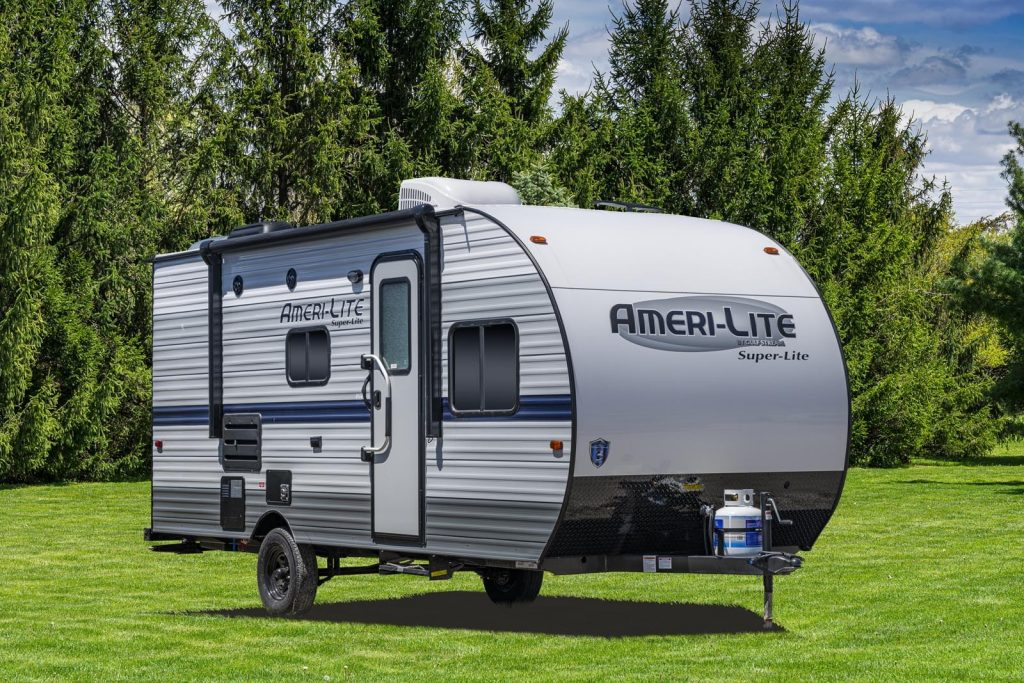 a Gulf Stream Coach RV trailer in a green lawn with a pleasant forested backdrop
