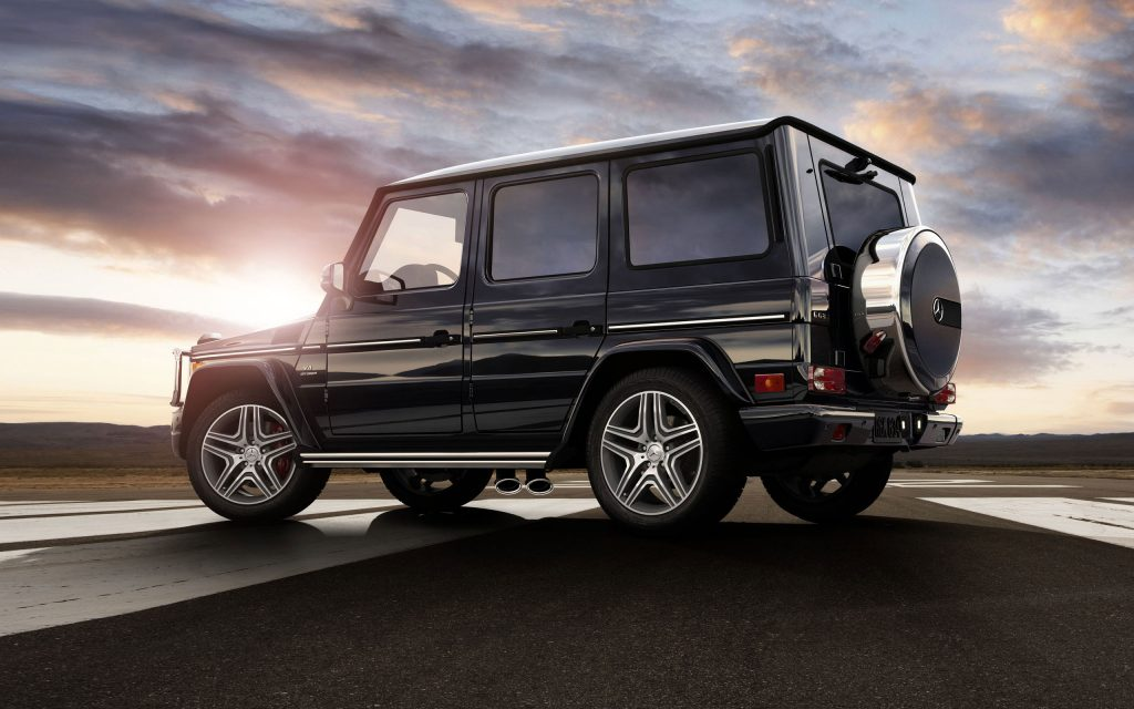 A black 2014 G-Class  SUV parked near the countryside.