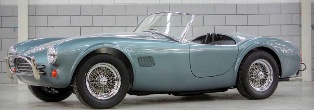 A pale blue AC Cobra roadster sits in a garage.