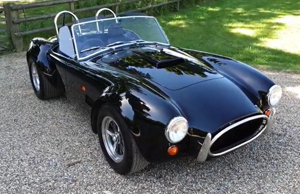A black AC Cobra convertible sits in a driveway