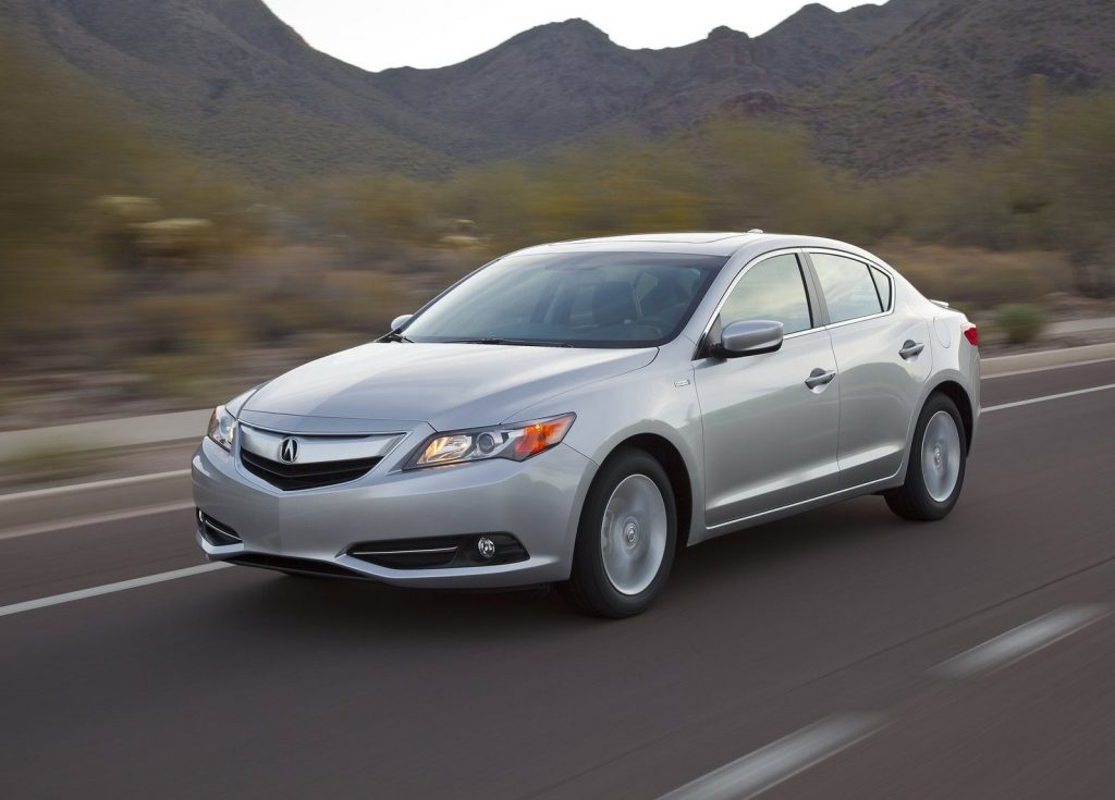 A silver 2013 Acura ILX drives down the road