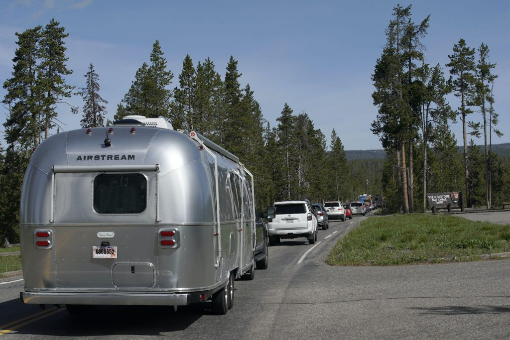 An Airstream RV trailer along with others, wait in a long line to enter the south entrance to Yellowstone National Park