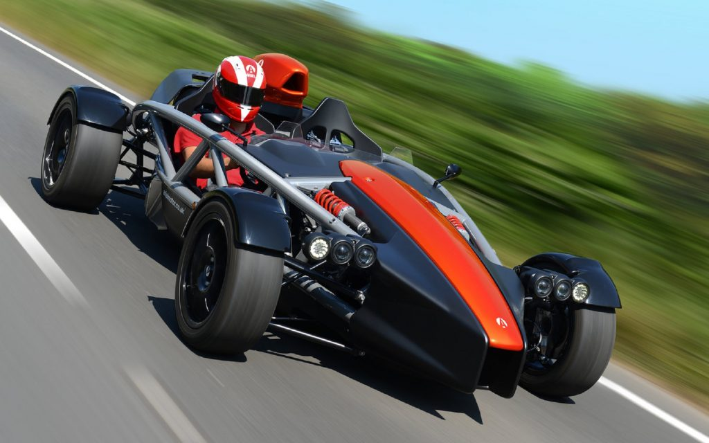 Red Ariel Atom 4 being driven by a helmeted driver down a country road