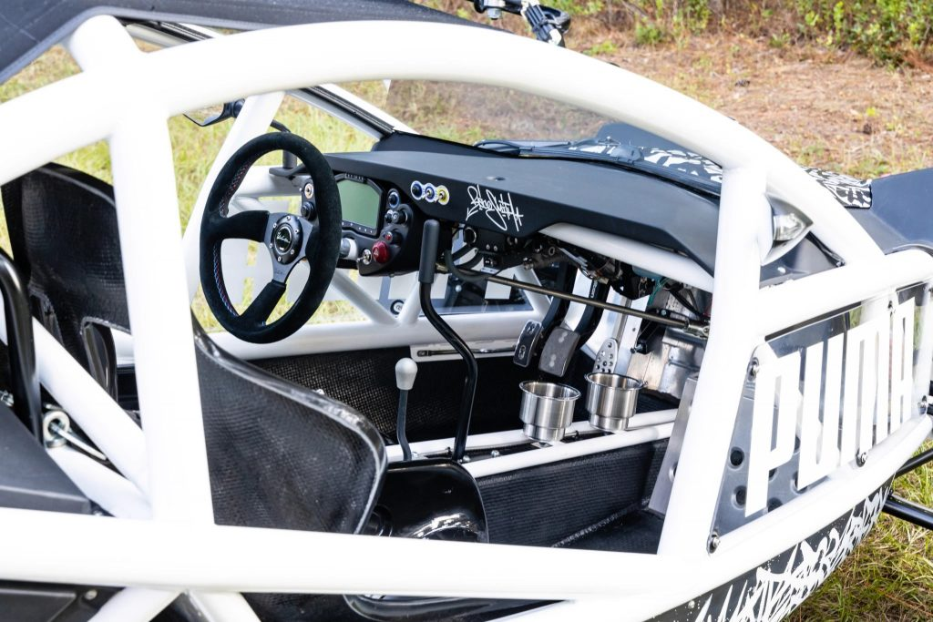 The cabin of the Ariel Nomad Tactical, showing the steering wheel, pedals, and seats