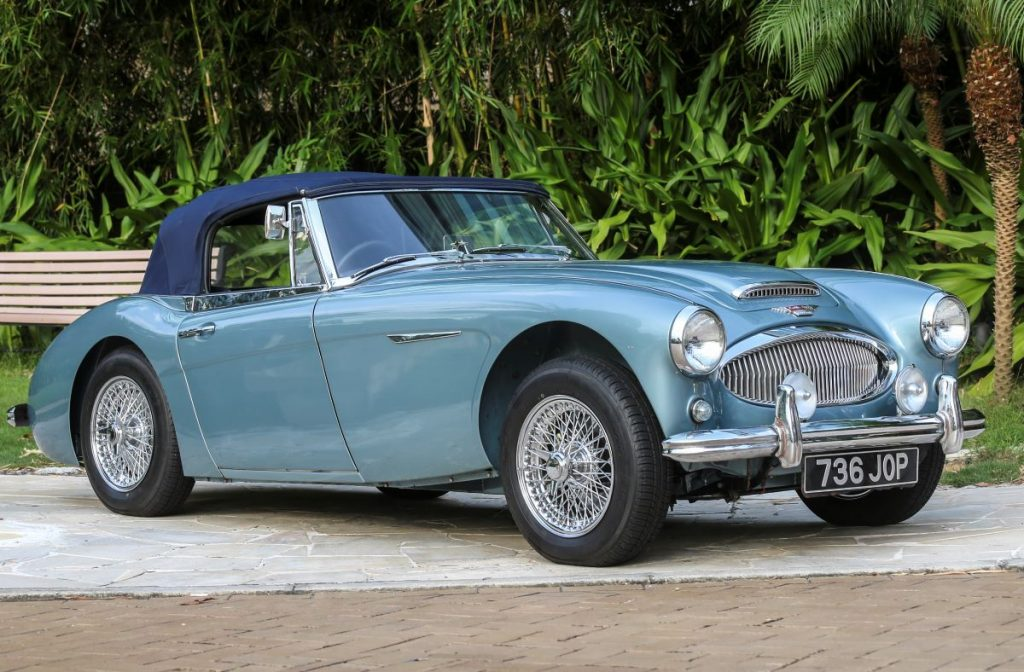 A sky-blue Austin-Healey convertible sits on display at a car show.