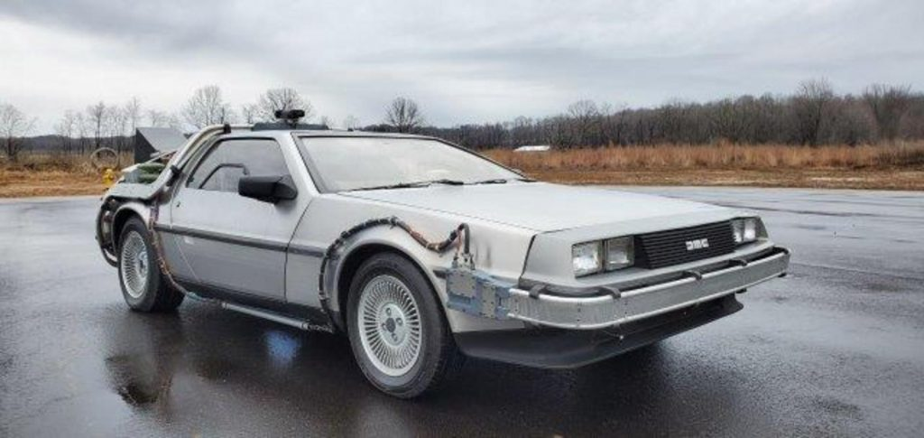 The Back to the Future replica Delorean movie car sitting in a wet parking lot.