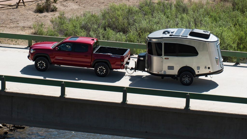 The Airstream Basecamp travel trailer is pulled behind a red Toyota pickup.