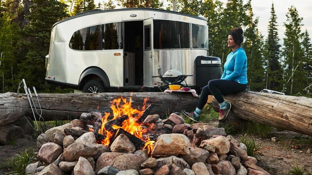 The Airstream Basecamp travel trailer is parked by a campfire.