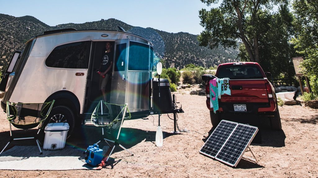 The Airstream travel trailer is by a campsite, a truck, and solar panels.