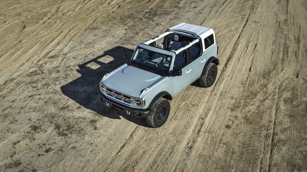 A gray four door bronco is on a dirt road and has its front and mid section tops off.