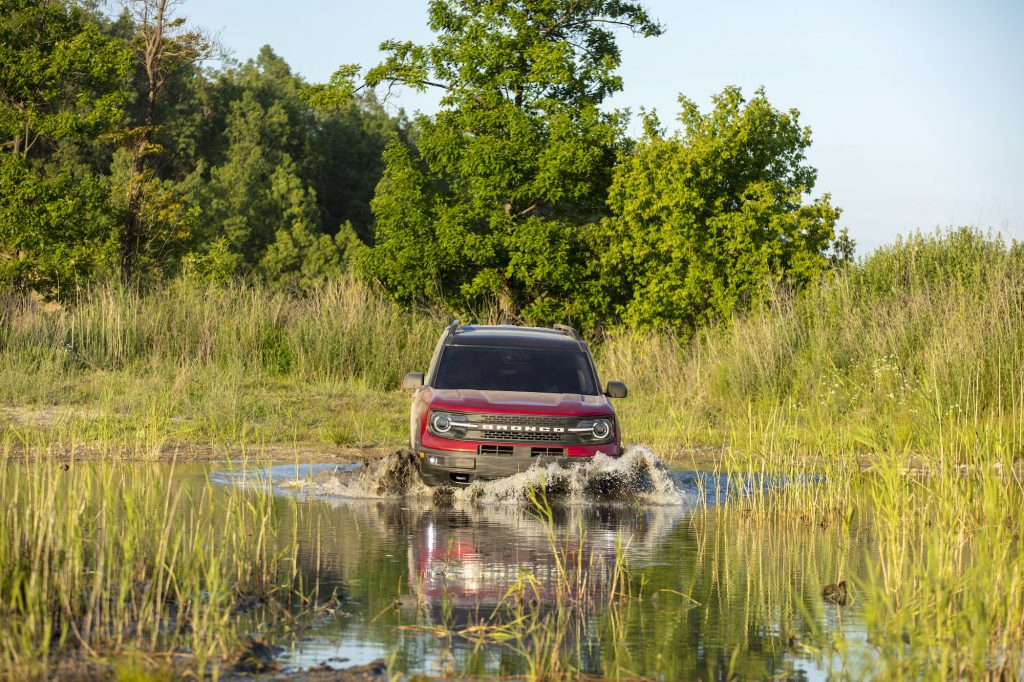 The Ford Bronco Sport, like this red one fording a deep puddle, is wild enough for most climbers
