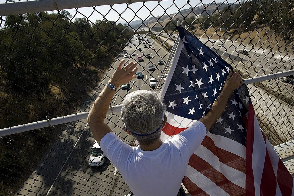 boy waves flag on overpass with freeway below