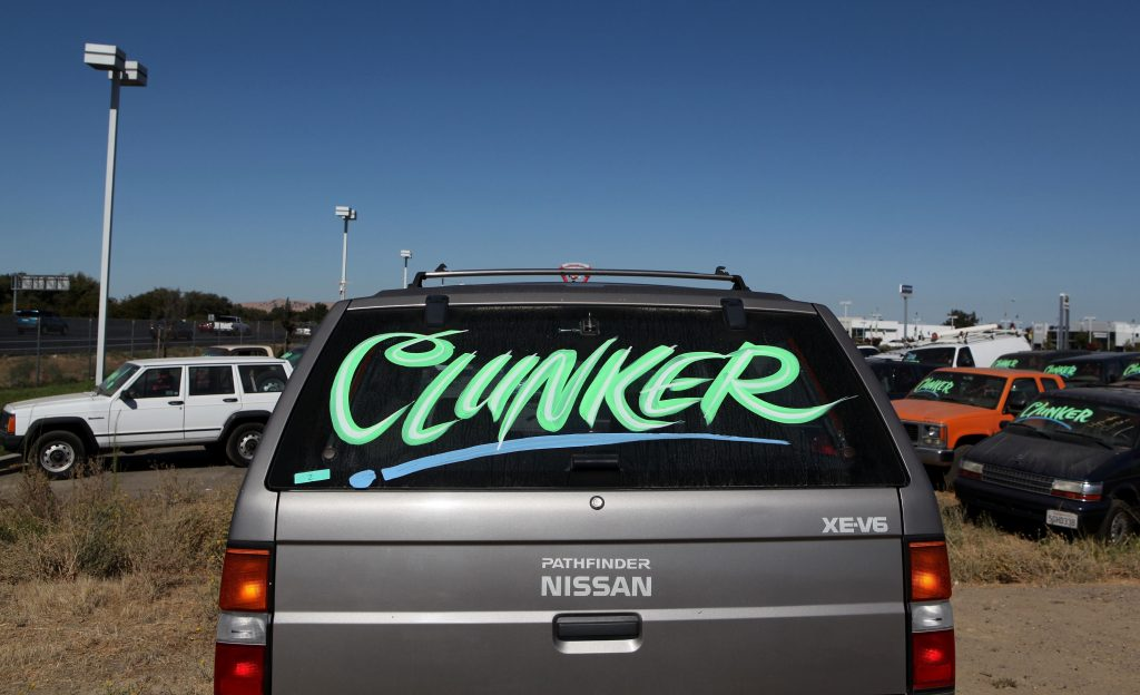 """The rear of an old SUV has """"Clunker"""" written across the liftgate glass."""