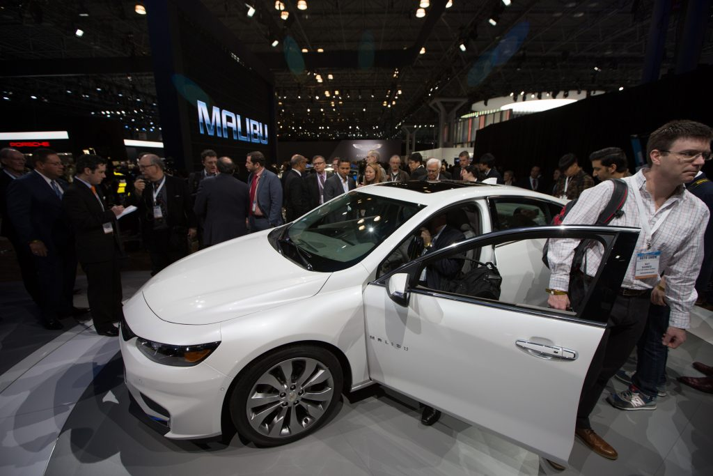 People checking out a Chevy Malibu at an auto show