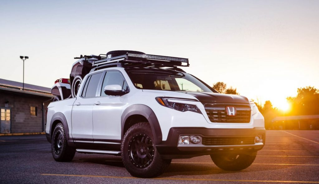 A custom white Honda Ridgeline has had some offroad upgrades, like fender flares, a roof rack, and a lift kit.