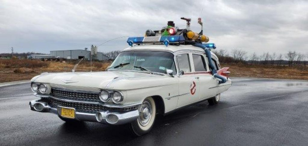 The Ecto-1 Cadillac movie car sitting in a wet parking lot.