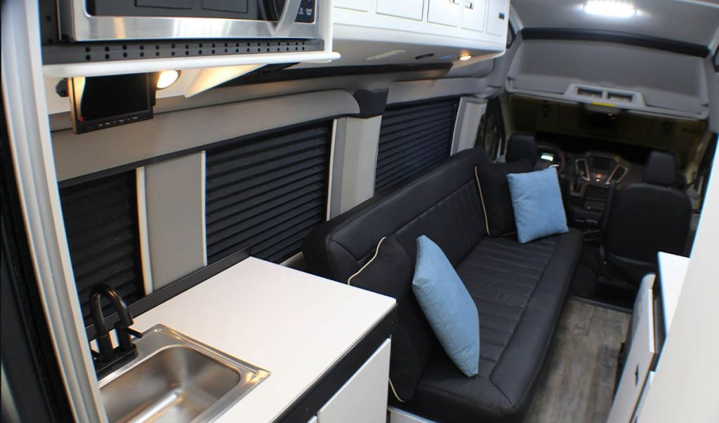 The interior of the RV has a black sofa and a small kitchen.
