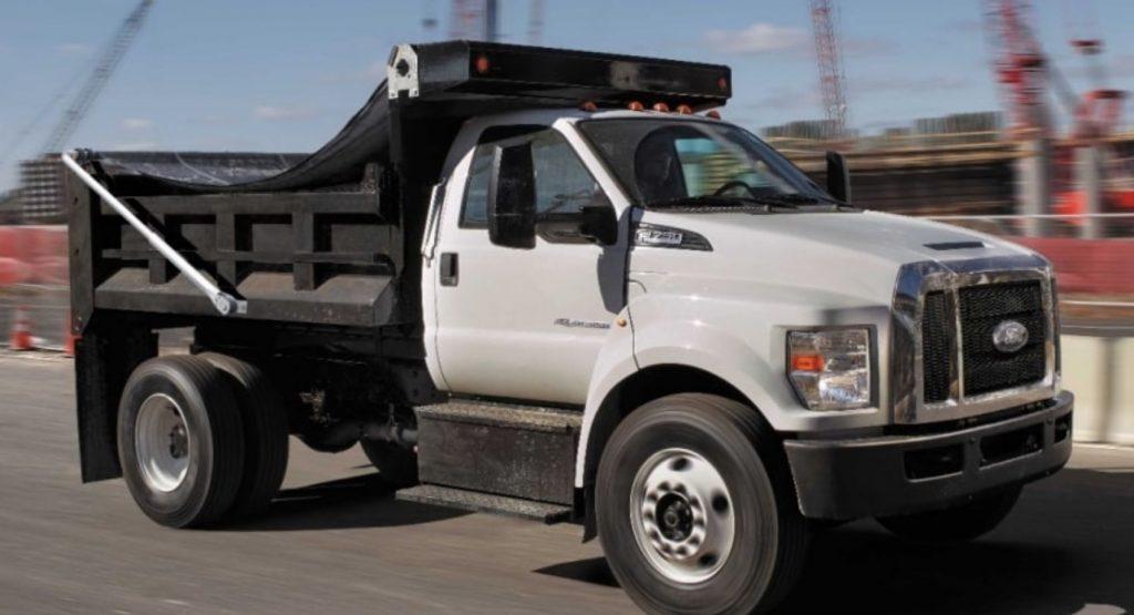 A white F-750 dump truck on a roadway near a construction site.