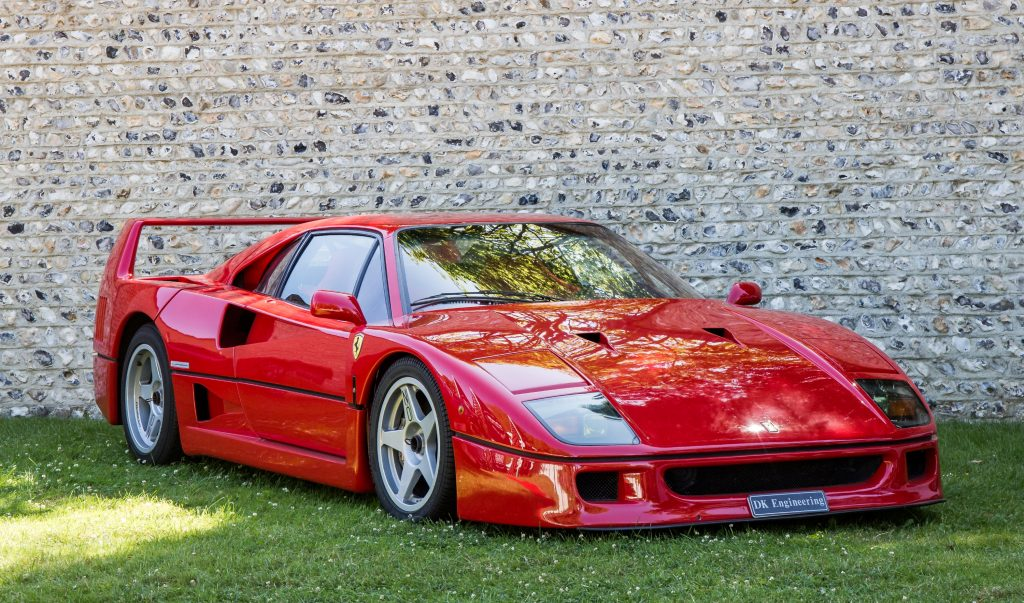 A red Ferrari F40 sits on the grass on display at a car show.