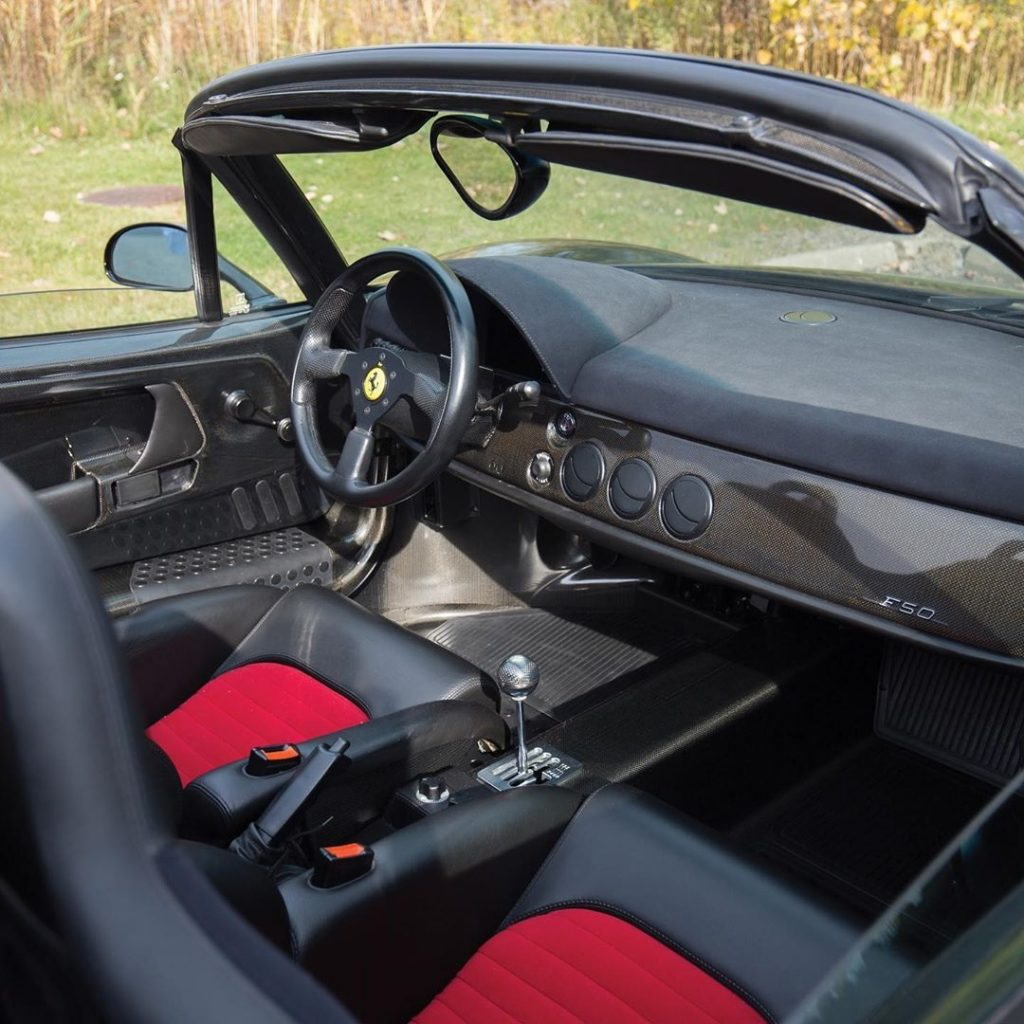 Interior shot of the Ferrari F50, showing the exposed carbon fiber, red-insert sport seats, and gated manual