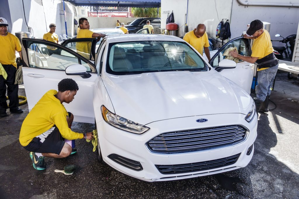 A white Ford Fusion at a car wash with several workers carefully polishing it